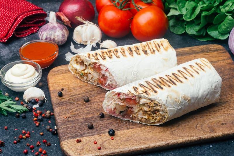 Doner-Kebab shawarma oder doner Verpackung Gegrilltes Huhn auf lavash Pittabrot mit Frischgemüse - Tomaten, grüner Salat, lizenzfreies stockbild