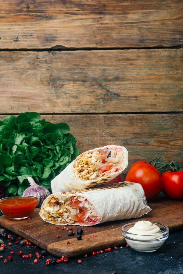 Doner-Kebab shawarma oder doner Verpackung Gegrilltes Huhn auf lavash Pittabrot mit Frischgemüse - Tomaten, grüner Salat, lizenzfreie stockbilder