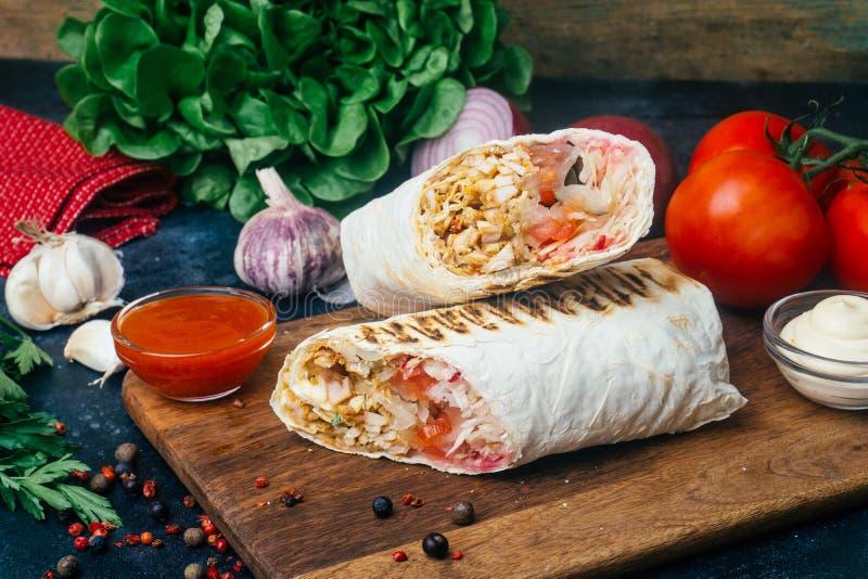 Doner-Kebab shawarma oder doner Verpackung Gegrilltes Huhn auf lavash Pittabrot mit Frischgemüse - Tomaten, grüner Salat, stockfotografie