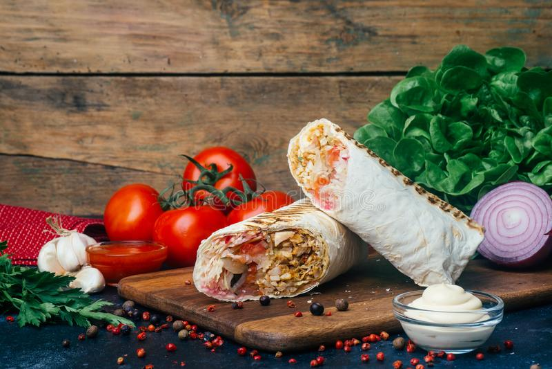 Doner-Kebab shawarma oder doner Verpackung Gegrilltes Huhn auf lavash Pittabrot mit Frischgemüse - Tomaten, grüner Salat, stockbild
