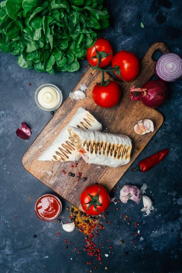 Doner-Kebab shawarma oder doner Verpackung Gegrilltes Huhn auf lavash Pittabrot mit Frischgemüse - Tomaten, grüner Salat, lizenzfreie stockfotografie