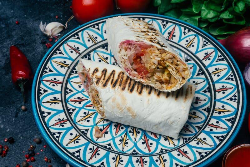 Doner-Kebab shawarma oder doner Verpackung Gegrilltes Huhn auf lavash Pittabrot mit Frischgemüse - Tomaten, grüner Salat, stockfoto