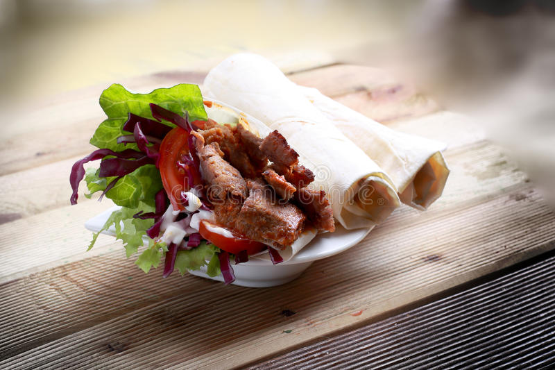 Doner kebab wrap. A durum is a wrap that is usually filled with typical doner kebab ingredients. The wrap is made from lavash or yufka flatbreads royalty free stock photos