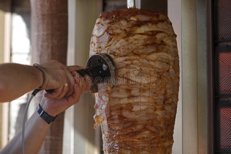 Doner, kebap, shawarma. Döner kebap is a Turkish dish made of meat cooked on a vertical rotisserie, normally lamb but sometimes beef, or chicken. In British royalty free stock images