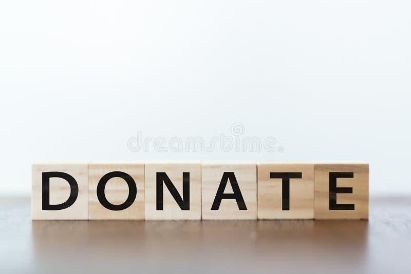 Donera ordet som är skriftligt på träkuber royaltyfri bild