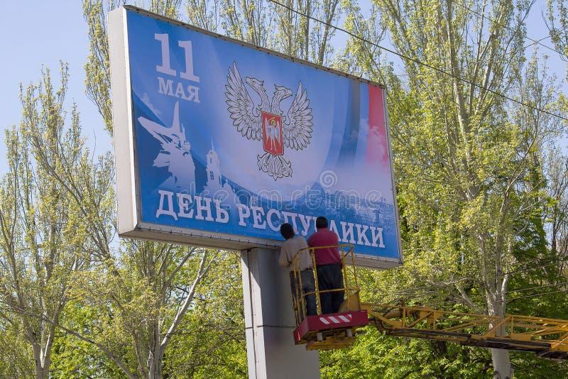 Donetsk, de Oekraïne - April 29, 2017: De arbeiders lijmen Banner tijdens het voorbereidingen treffen voor de viering van de Dag  stock afbeelding