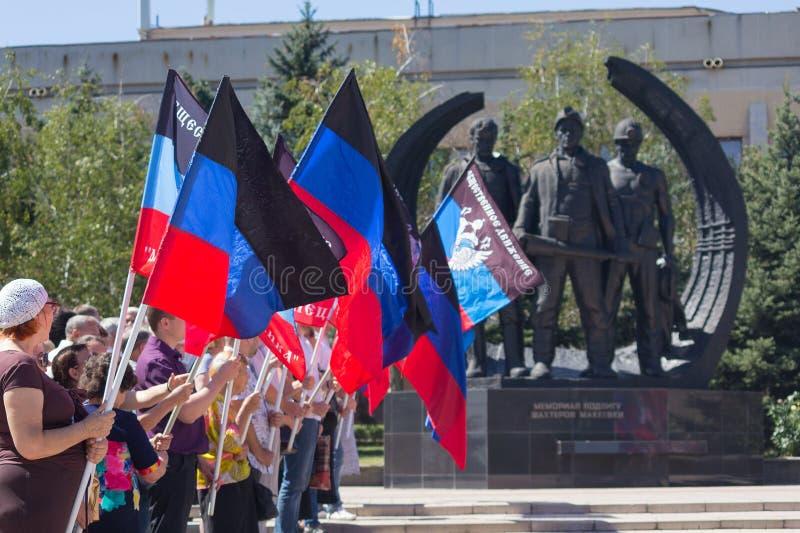 Donetsk, Ucrânia - 23 de agosto de 2018: Povos com as bandeiras da república do ` s dos povos de Donetsk que coloca flores no mem fotografia de stock