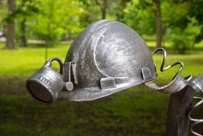Donetsk, Ucrânia - 9 de maio de 2017: O capacete do ` s do mineiro forjou as figuras forjadas do metal foto de stock