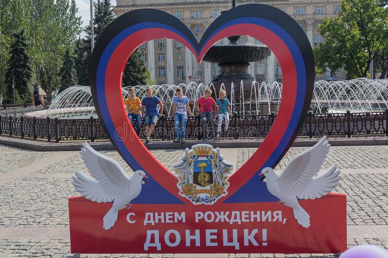 Donetsk, Ukraine - August 26, 2017: Children at the fountain and the symbolism of the self-proclaimed state in the central square royalty free stock photography