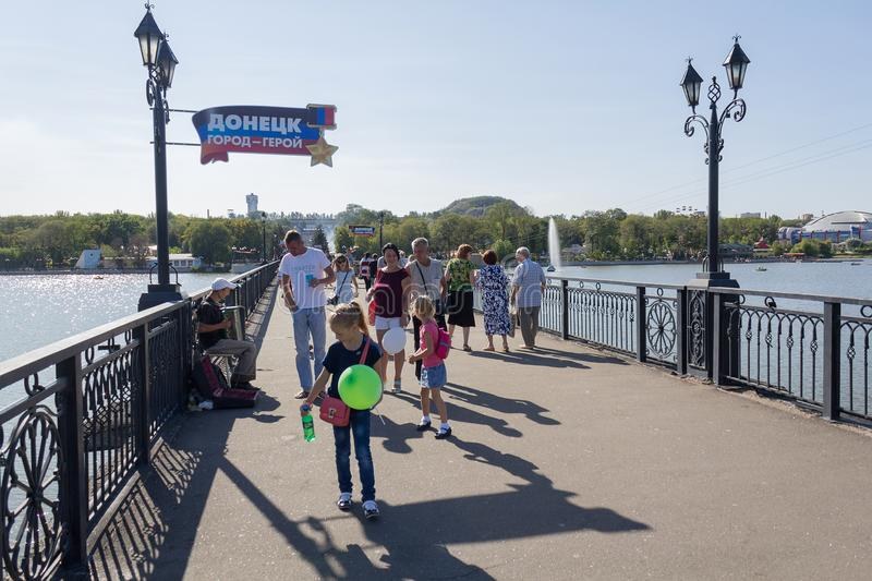 Donetsk, Ukraine - August 26, 2018: People on the bridge in the park Shcherbakova. The inscription on the index: `Donetsk - the city of the hero` in Russian stock photo