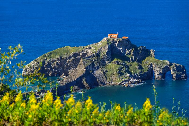 Doniene Gaztelugatxeko hermitage on top of Gaztelugatxe island and with yellow flowers in the foreground. Biscay, Basque Country,. Spain royalty free stock photo