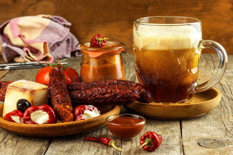 Donker bier in een glas en kruidige worsten met Spaanse peperpeper Droge worsten op de lijst stock afbeeldingen