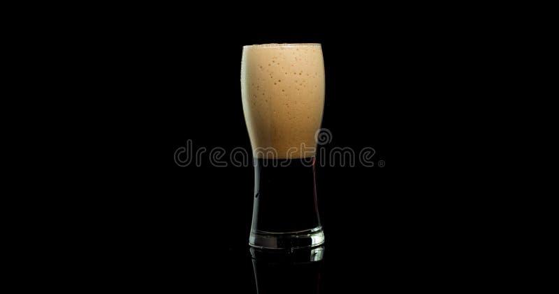 Donker bier in een glas met schuim op een zwarte achtergrond royalty-vrije stock foto