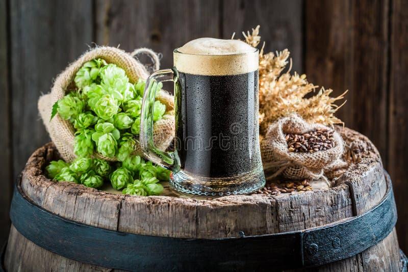 Donker bier met schuim, tarwe en hop op oud vat royalty-vrije stock afbeeldingen