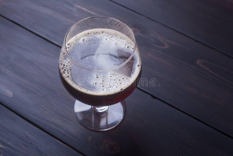 Donker bier op hout stock foto's