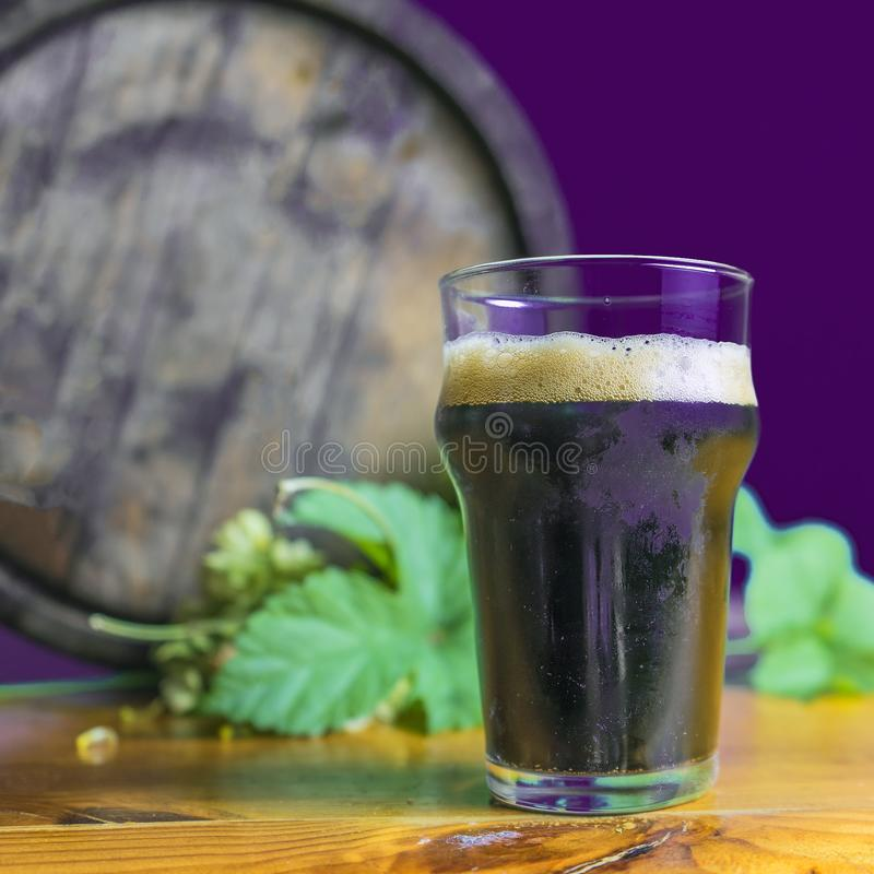 Donker bierglas op de lijst met hop op de achtergrond van vaten stock afbeelding