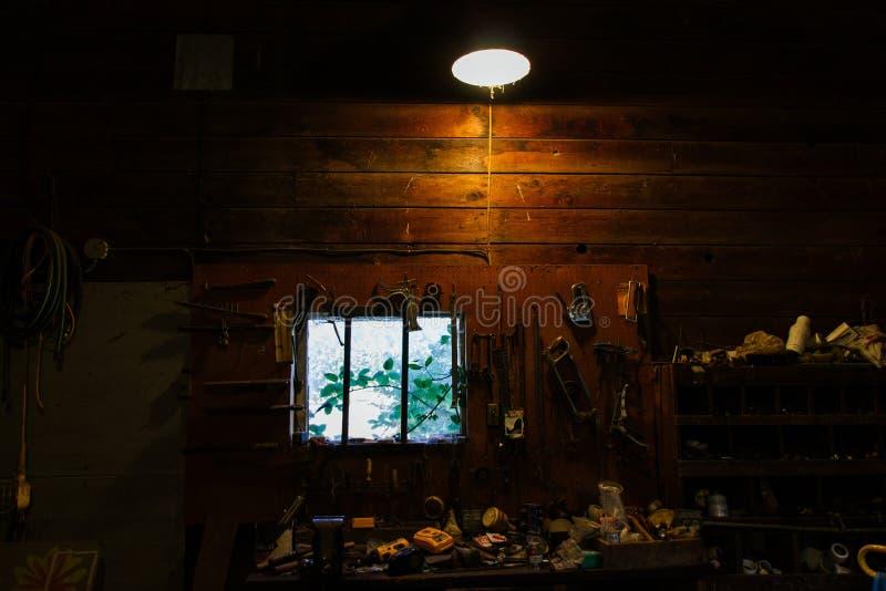 Donker binnenland van een slordige houten werkbank met allerlei rond geworpen hulpmiddelen stock fotografie