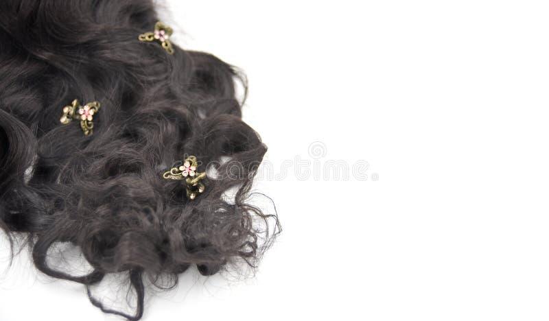 Donker bruin krullend haar met koper en kristaljuwelen op de witte achtergrond stock foto