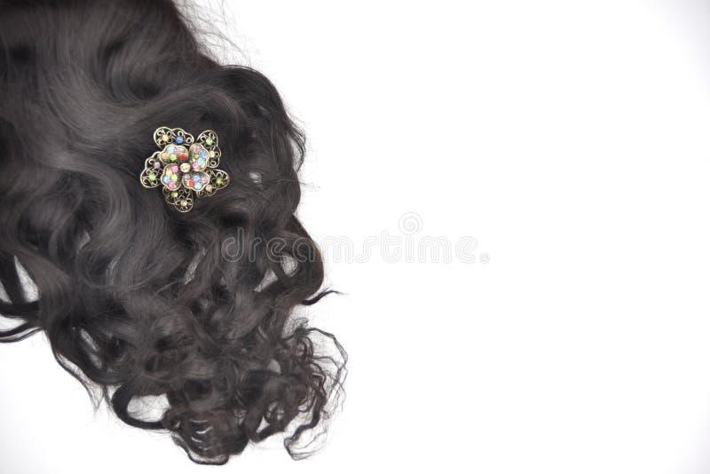 Donker bruin krullend haar met multicoloured kristaljuwelen op de witte achtergrond stock afbeelding
