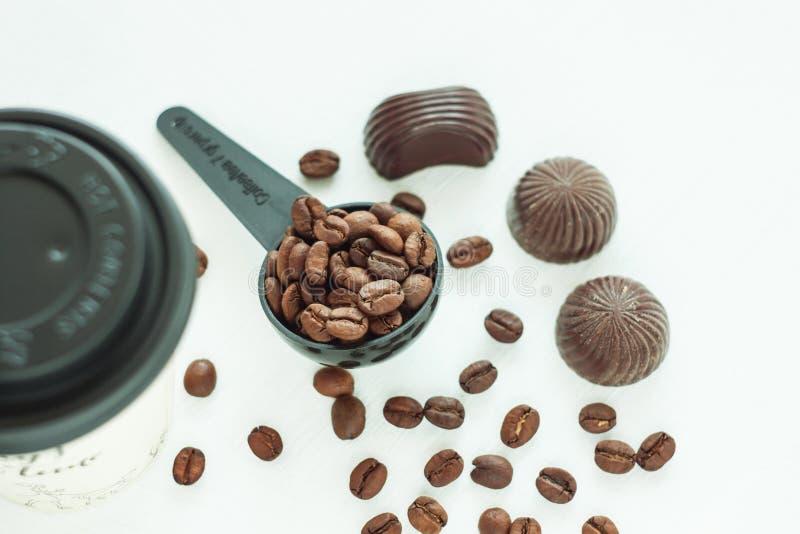 Donker chocoladesuikergoed, snoepjes met een lepel van koffiebonen op lichte achtergrond Bevat gradi?nt en het knippen masker royalty-vrije stock foto's