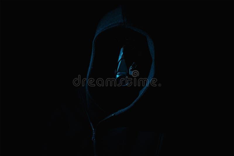 Donker en sinister met een masker op cijfer in een kap tegen zwarte royalty-vrije stock foto's