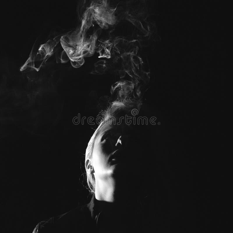Donker en somber schot van het jonge vrouw roken stock foto's