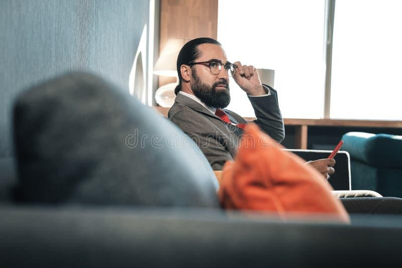 Donker-eyed rijpe zakenman die wat vrije tijd vóór vergadering hebben royalty-vrije stock foto's