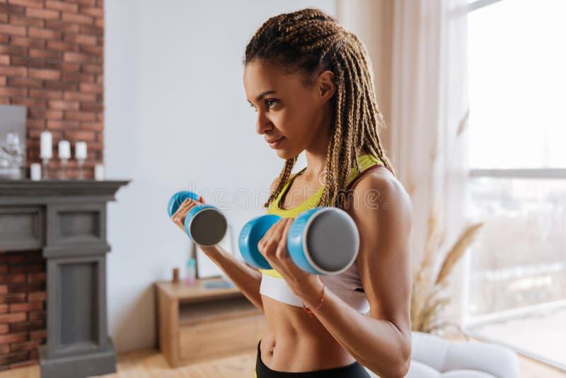 Donker-eyed sportvrouw die met handgewichten thuis uitwerken royalty-vrije stock afbeelding