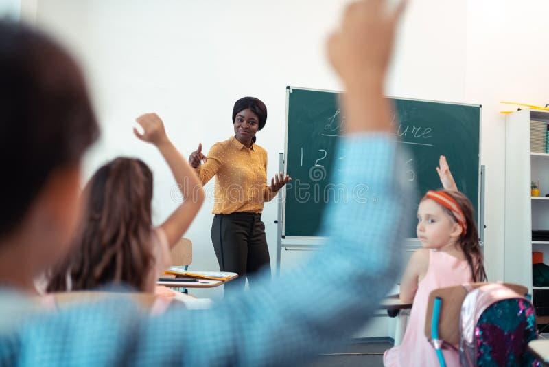 Donker-gevild leraarsgevoel tevreden met het werk van leerlingen royalty-vrije stock foto's