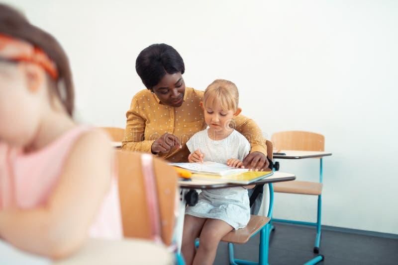 Donker-gevilde leraar die het gelukkige werken met kinderen voelen royalty-vrije stock afbeeldingen