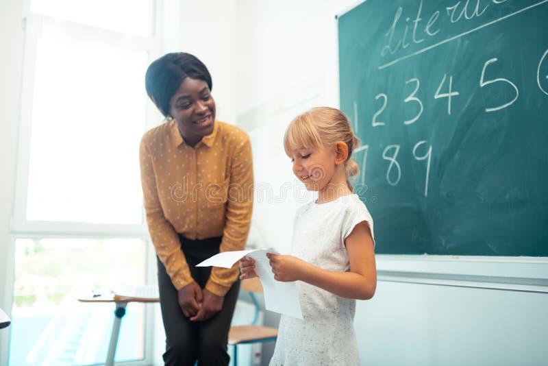 Donker-gevilde leraar die met leerling dichtbij bord spreken stock foto