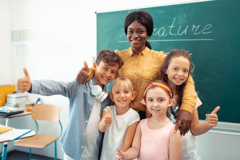 Donker-gevilde leraar die vrolijk met haar grappige slimme leerlingen voelen royalty-vrije stock afbeeldingen