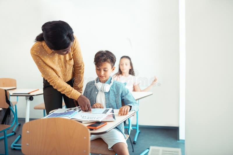 Donker-gevilde leraar die zich dichtbij knappe slimme leerling bevinden stock foto
