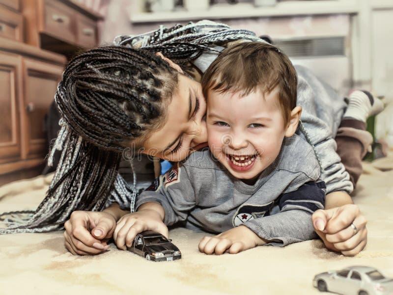 Donker-gevilde moederspelen met haar zoon Latijns-Amerikaanse Mammaspelen en lach met zijn kleine zoon Concept: Gelukkige Moeder` royalty-vrije stock afbeelding