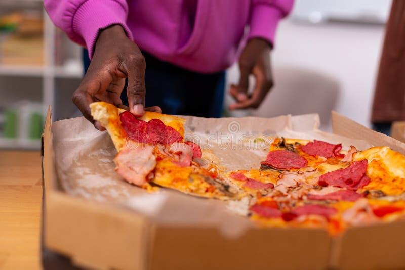 Donker-gevilde tiener die stuk van pizza met bacon en pepperonis nemen stock foto's
