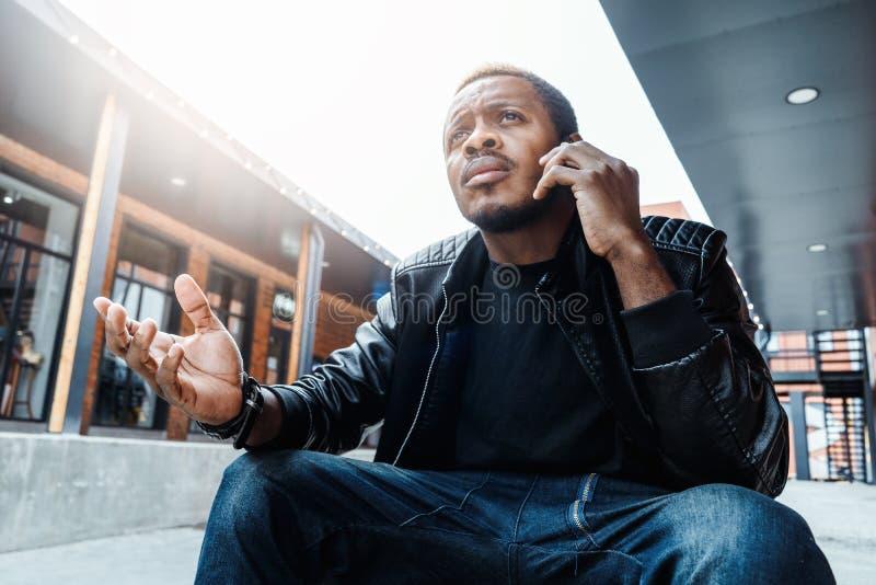 Donker-gevilde unpleasantly verraste en geërgerde mens die door mobiele telefoon spreken royalty-vrije stock foto's