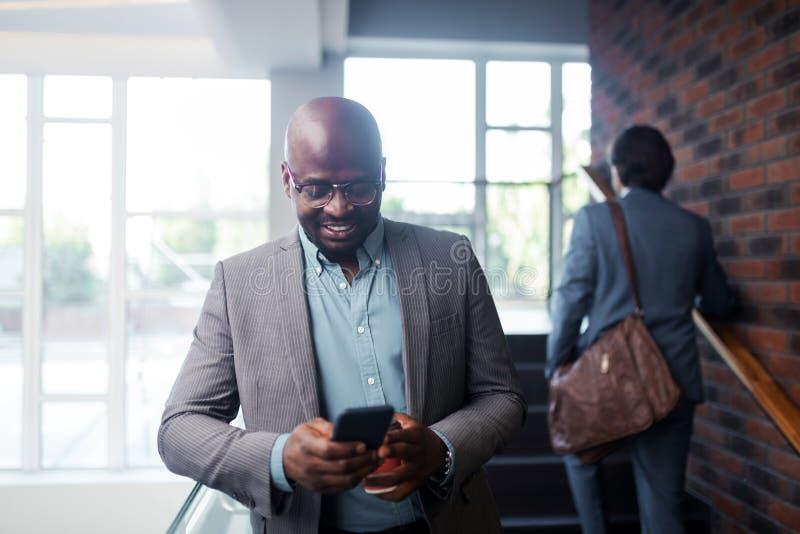Donker-gevilde zakenman die glazen dragen die terwijl het lezen van bericht glimlachen stock afbeelding
