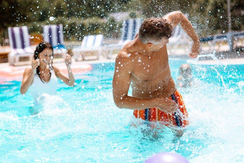 Donker-haired echtgenoot bespattend water op vrouw in zwembad royalty-vrije stock fotografie