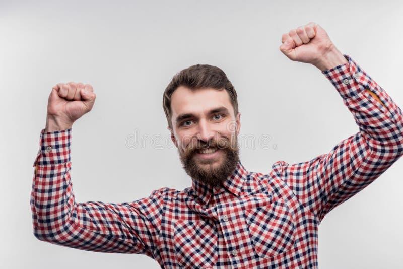 Donker-haired gebaarde beambte die gelukkig na het beëindigen van project voelen stock afbeeldingen