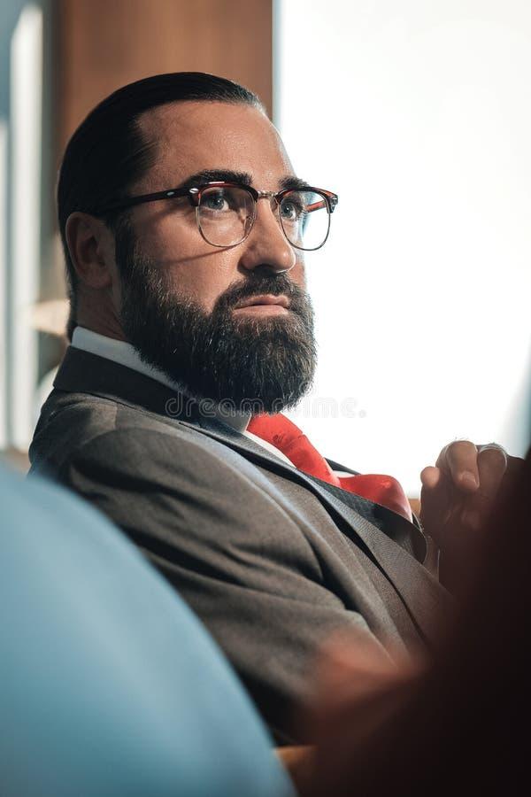 Donker-haired gebaarde econoom die glazen dragen die op bank zitten stock foto