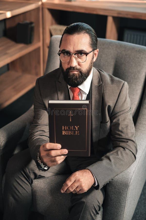 Donker-haired gebaarde mens die de Heilige Bijbel houden stock foto's
