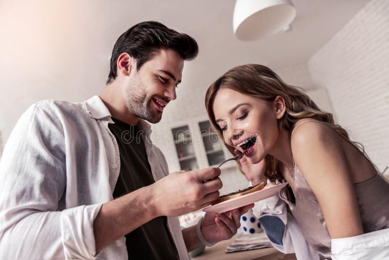 Donker-haired gebaarde mens in een wit overhemd en zijn mooie vrouw die het verbazen voelen stock foto