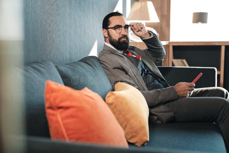 Donker-haired gebaarde zakenman die kostuumzitting op bank dragen stock foto