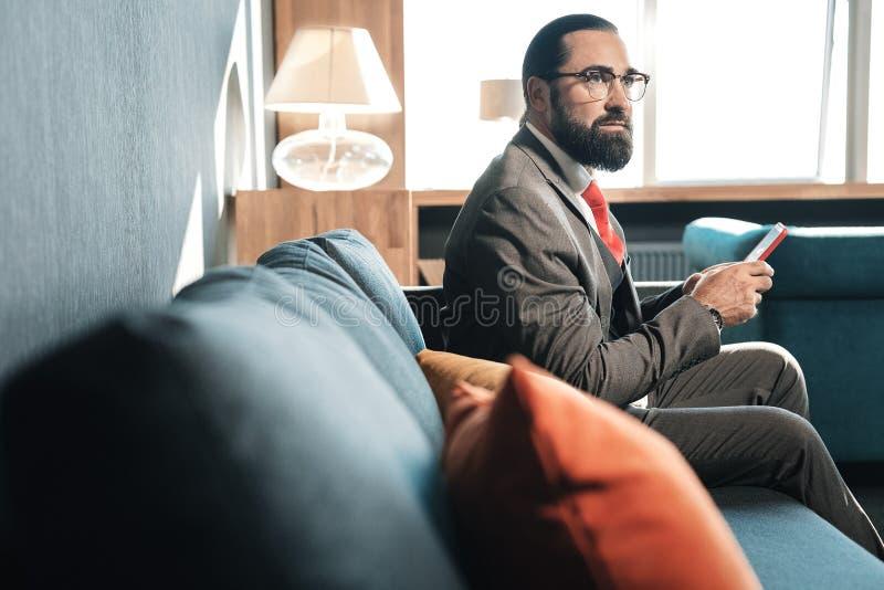 Donker-haired gebaarde zakenmanzitting in comfortabele hotelruimte royalty-vrije stock foto