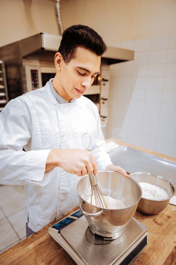 Donker-haired jong bakker het ranselen wit van de eieren voor gebakje royalty-vrije stock afbeeldingen