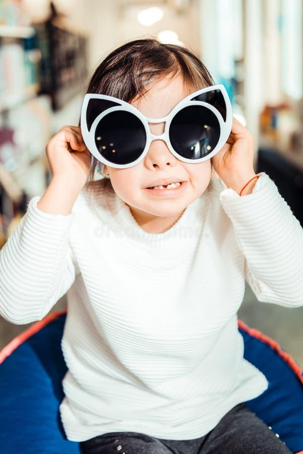 Donker-haired jong meisje in witte sweater die op reuzezonnebril proberen royalty-vrije stock foto