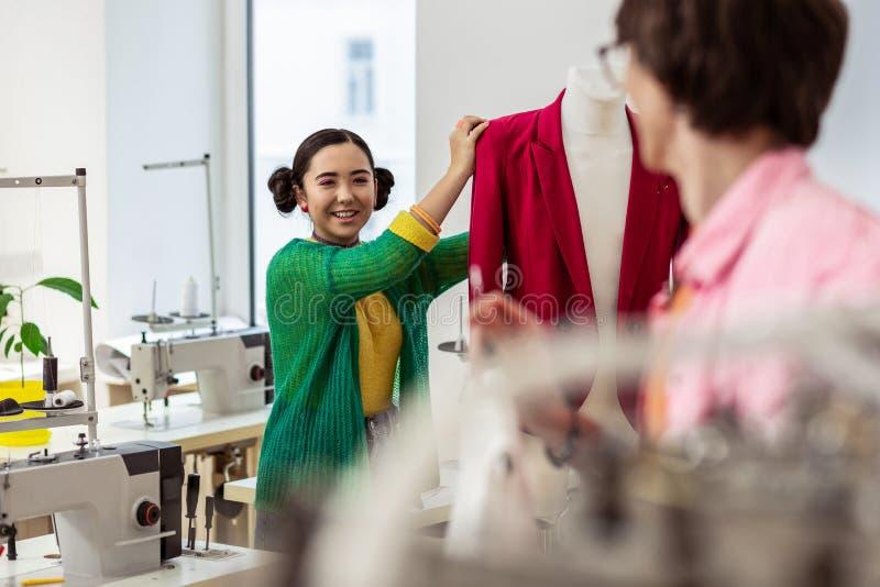 Donker-haired jonge Aziatische ontwerper in het groene cardigan helder glimlachen stock foto's