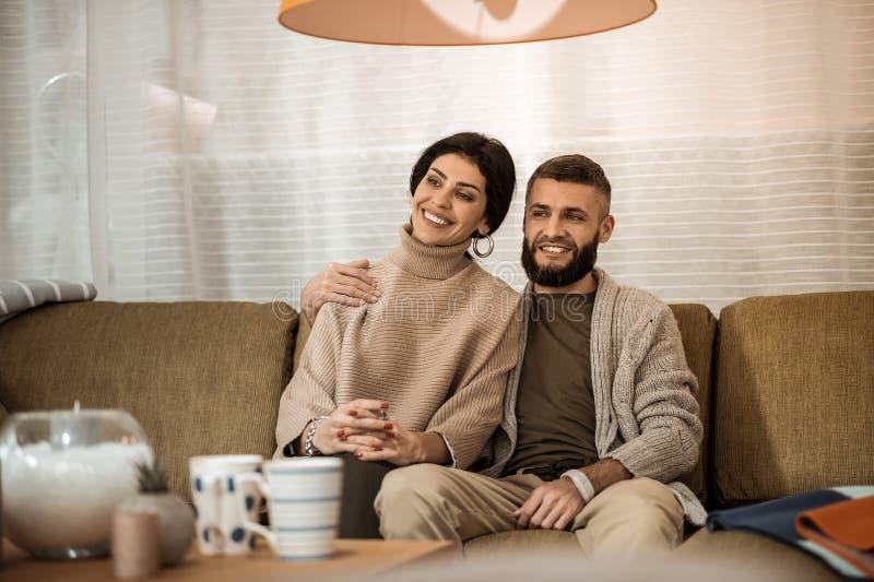Donker-haired leuke paarzitting uiterst dicht bij elkaar terwijl het letten van op TV stock foto