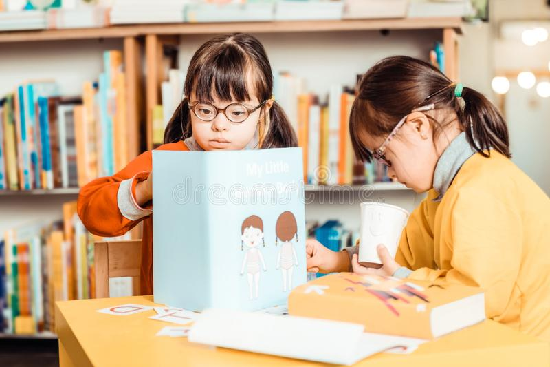 Donker-haired meisjes in heldere overhemden die bezig met scholingsmateriaal zijn stock afbeeldingen