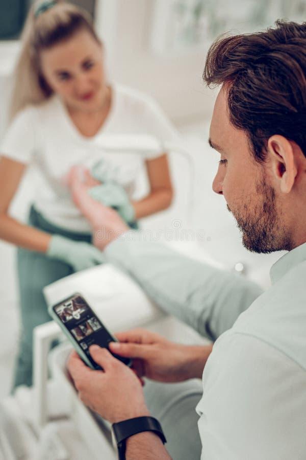 Donker-haired nieuwsgierige mens die zijn smartphone controleren terwijl langharige meester royalty-vrije stock foto